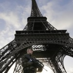 A French soldier stands alert at the Eiffel Tower which remained closed on the first of three days of national mourning in Paris, Sunday, Nov. 15, 2015. Thousands of French troops deployed around Paris on Sunday and tourist sites stood shuttered in one of the most visited cities on Earth while investigators questioned the relatives of a suspected suicide bomber involved in the country's deadliest violence since World War II. (AP Photo/Amr Nabil)